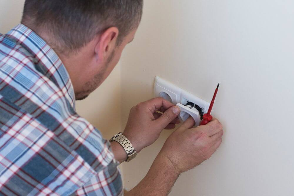 a man fixing a white outlet on the wall
