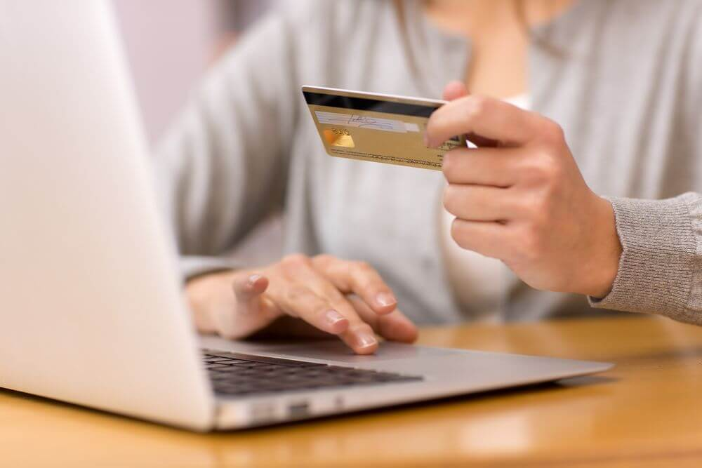 woman wearing a gray sweater holding a gold credit card in front of her laptop about to pay online