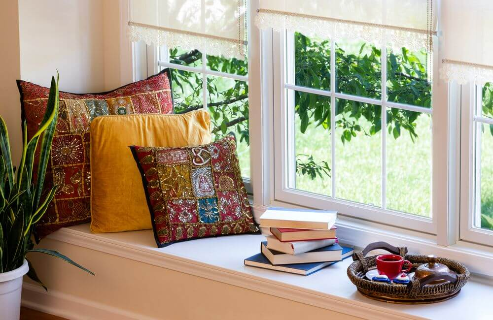 a cozy window-bench with three pillows, books and a hot beverage