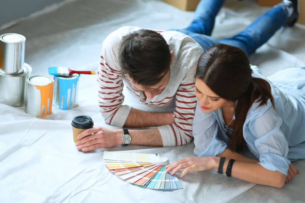 man and woman laying on a sheet on the floor looking at paint swatches