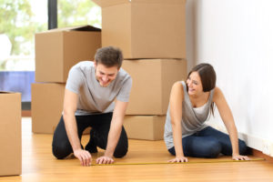 couple measuring the floor in their house with boxes behind them