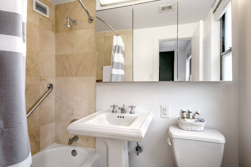 a small brown bathroom with a large mirror above the sink and the toilet