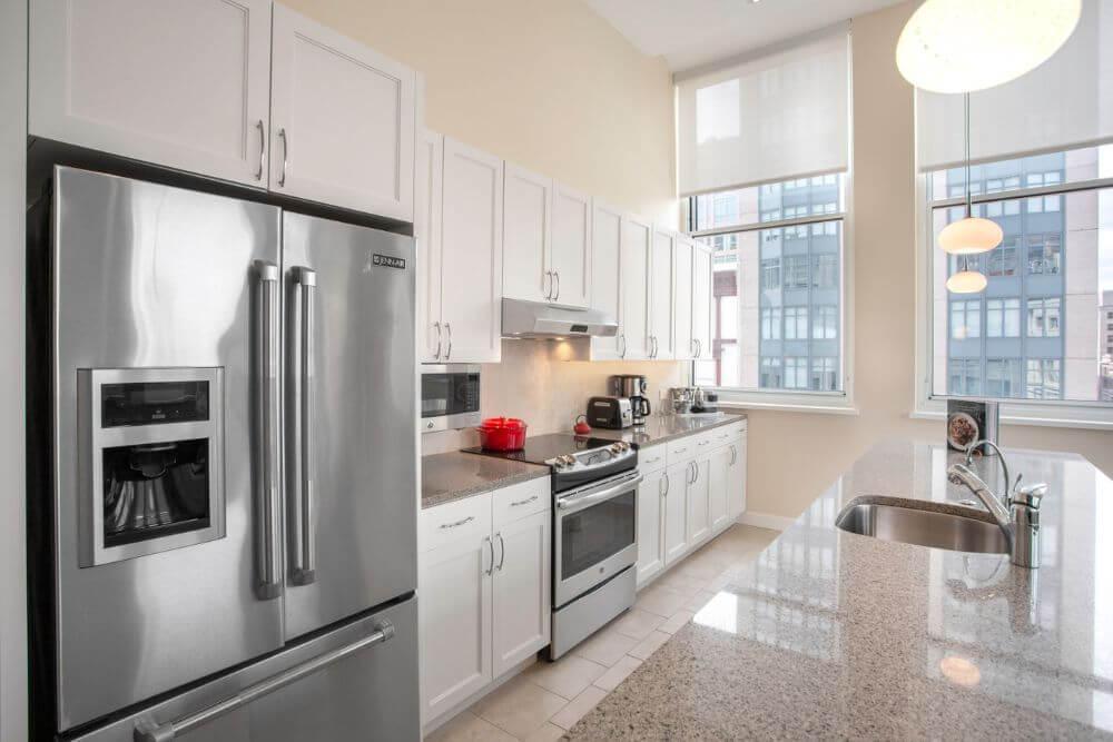 large white kitchen with a marble counter top and a large stainless steel double door refrigerator