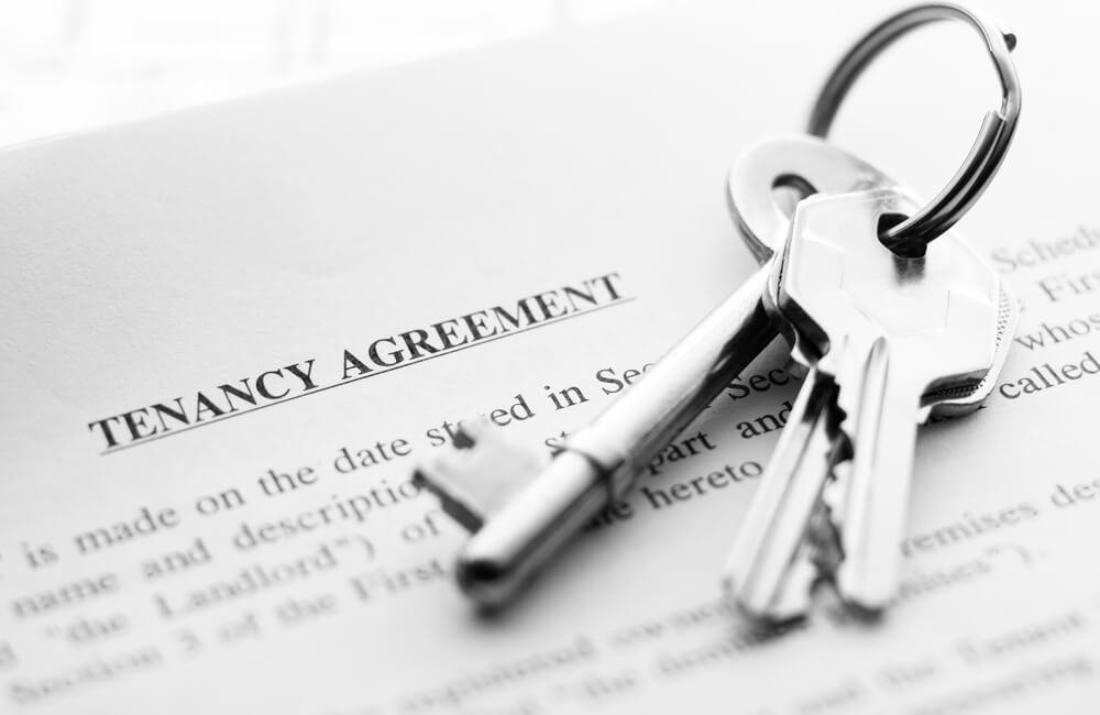 Paper with underlined Tenancy agreement title with silver keys on top