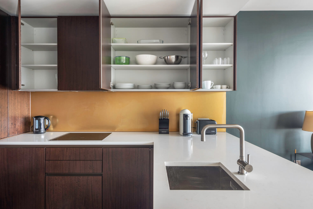 Modern kitchen with dark wooden cupboards and white counter that has some kitchen appliances on it. There are some cupboard above the counters that are open and have some cutlery and plates inside
