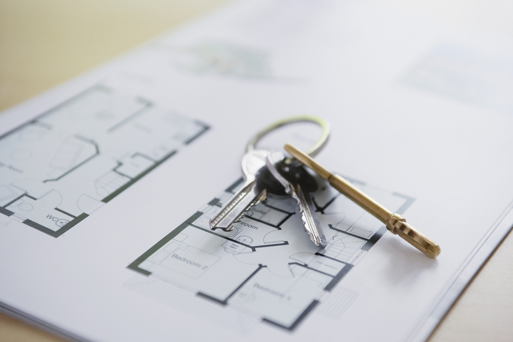 Blueprint of an apartment with three keys attached to one key ring on top